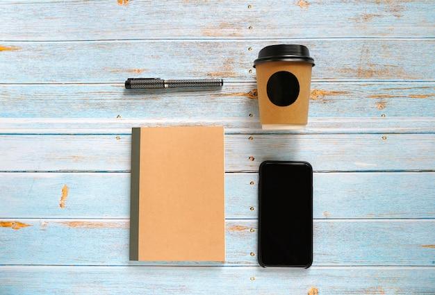 Mock up arbeitsbereich von smartphone, notebook, kaffee und stift auf blauem holztisch wegnehmen