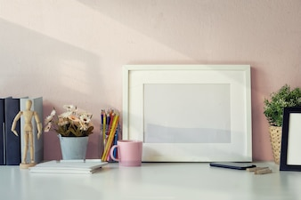 Mock-up-Arbeitsplatz-Tisch mit weißen Posterrahmen, Kaffeetasse, Notebook und Zubehör.