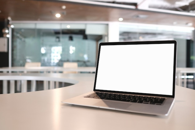 Mock up blanko-laptop mit weißem bildschirm auf holzschreibtisch in moern zimmer.