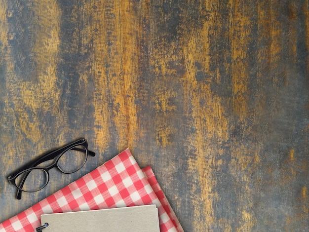 Mock-up brille und buch auf der ebene von rot und weiß auf altem holz.