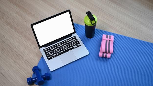 Mock-up-computer-laptop-hanteln, wasserflasche und matte auf dem boden. online-trainingskonzept für zu hause.