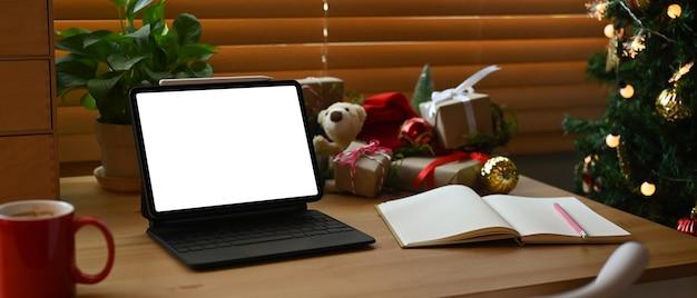 Mock-up-computer-notebook, kaffeetasse und weihnachtsgeschenke auf holztisch.