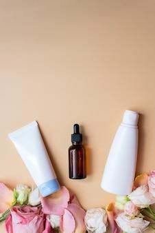 Mock-up-creme und lotion in weißen packungen und feuchtigkeitsspendendes serum in einer braunen glasflasche auf blauem hintergrund neben rosenblättern. das konzept der schaffung von naturkosmetik.