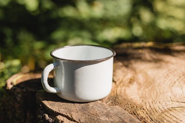 Mock-up der kaffeetasse am naturwald der grünen unschärfe.
