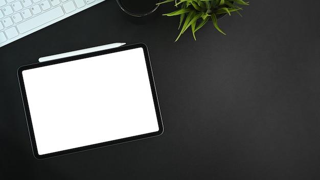 Mock-up digitales tablet mit leerem bildschirm, eingabestift, kaffeetasse und zimmerpflanze auf schwarzem leder.