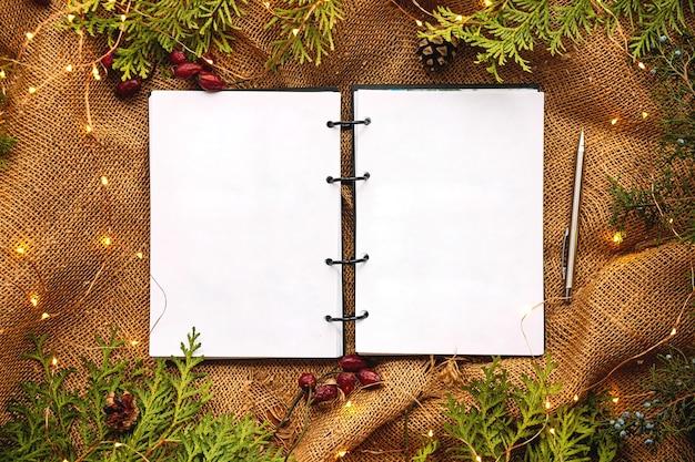 Mock-up-draufsicht auf notizbuch mit festlichem tannen- und sackleinenhintergrund