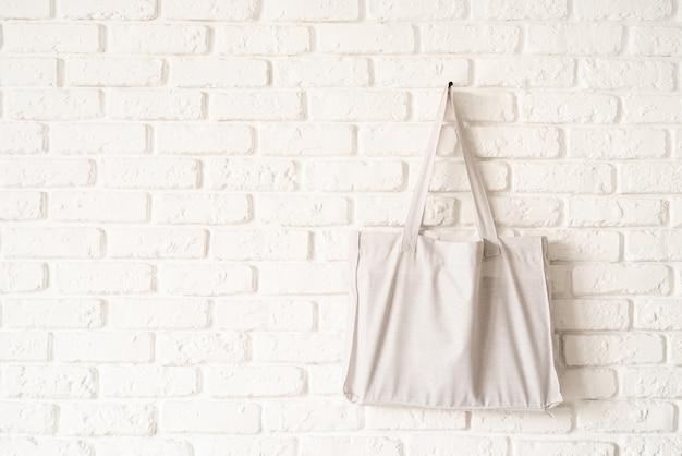 Mock up einkaufstasche aus weißem baumwollstoff auf weißem backsteinmauerhintergrund. speicherplatz kopieren