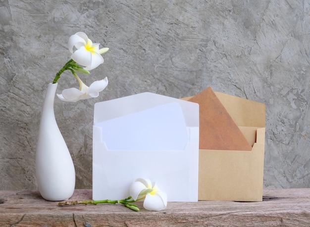 Mock-up-einladung braune karte und schöne plumeria-blumen in moderner weißer vase auf grunge-holztisch mit loft-wandhintergrund, grußkarte in sanftem ton-stillleben