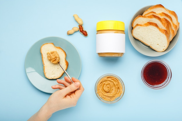 Mock-up für erdnussbutter, cremige erdnusspaste. draufsicht, flacher lay-prozess des kochens des frühstücks, brotaufstrich, toast mit erdnussbutter, cremige erdnusspaste durch weibliche hände auf blauem hintergrund