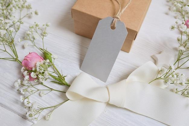 Mock up geschenkbox mit geschenkkarte und blumen im rustikalen stil