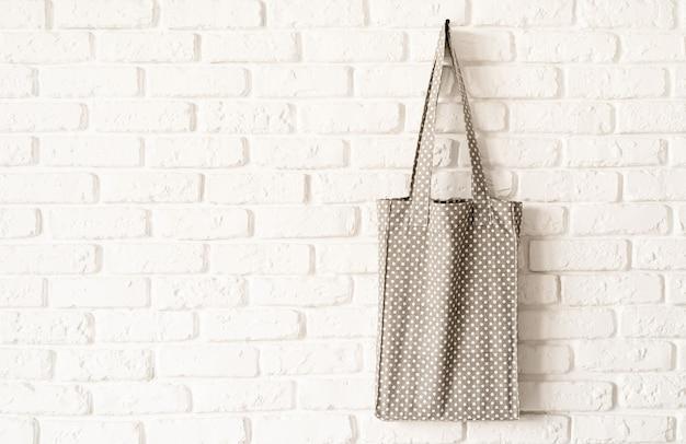 Mock up grau gepunktete einkaufstasche öko hipster weißen baumwollstoff auf weißen backsteinmauer hintergrund. speicherplatz kopieren