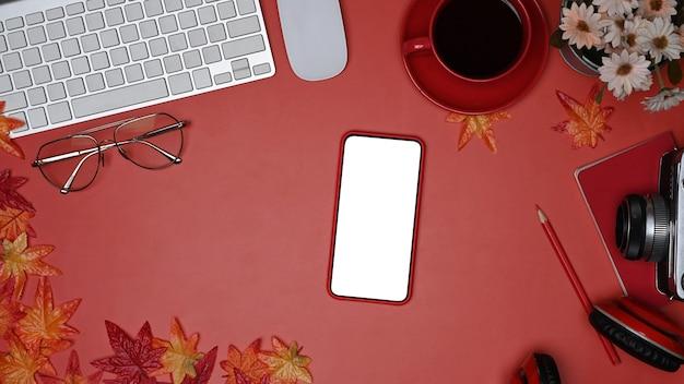 Mock-up handy, kaffeetasse, kamera und ahornblätter auf rotem hintergrund.
