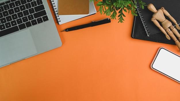 Mock-up handy, laptop, zimmerpflanze und notebook orange hintergrund.