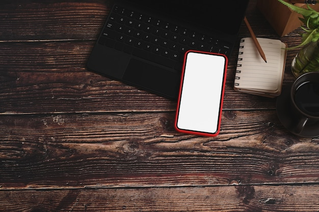 Mock-up-handy mit weißem bildschirm, laptop, notebook und pflanze auf holztisch.