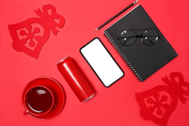 Mock-up-handy, notebook, rote tasse, dose und brille auf rotem hintergrund.