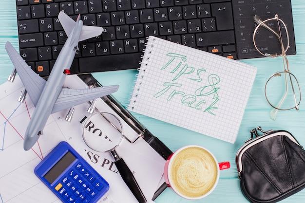 Mock-up-konzept mit bürobedarf und spielzeugflugzeug. tipps und track auf notebook geschrieben.