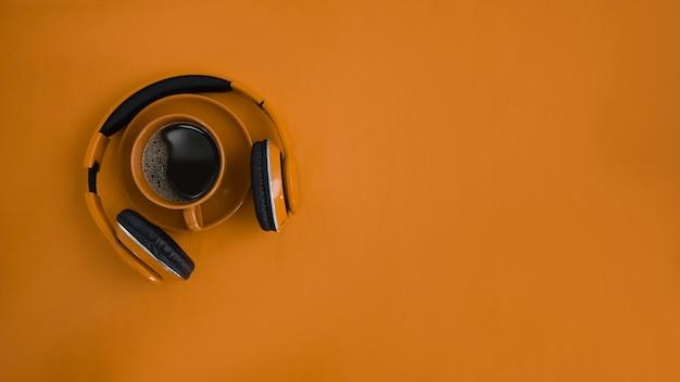 Mock-up-kopfhörer, kaffeetasse und kopienraum auf orangem hintergrund.