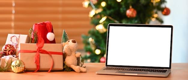 Mock-up-laptop-computer und weihnachtsgeschenkboxen auf holztisch.