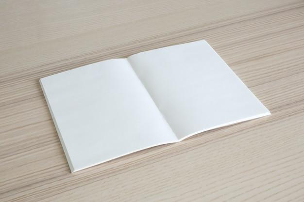 Mock up leeres offenes papierbuch auf holztischhintergrund
