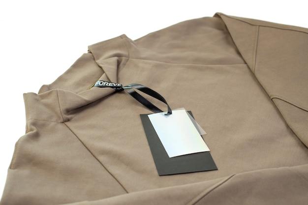 Mock up leeres schwarz-weißes etikett mit schwarzem satinband auf einem sumpfgrünen hoodie isoliert