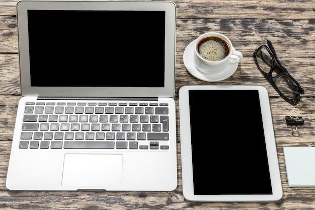 Mock-up mit tablet-pc, offenem laptop und haftnotizen auf holztisch. einfacher kreativer arbeitsbereich.