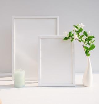Mock up poster weißen rahmen und schöne gardenia tropische blumen in modernen weißen vase dekor mit grüner kerze auf beige tisch und zement wandoberfläche mit langen schatten