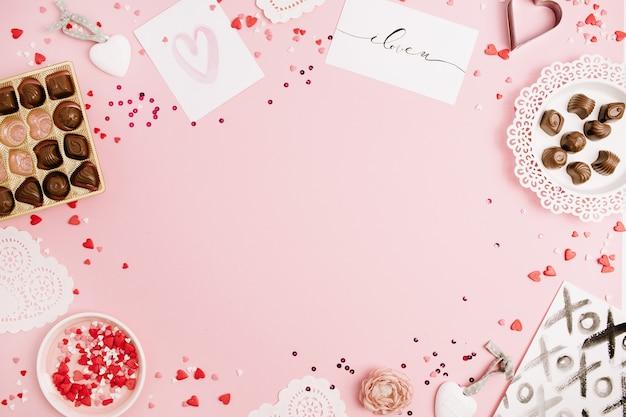 Mock-up-rahmen aus konfetti, herzsymbol-zubehör, süßigkeiten, postkarten auf rosa hintergrund. flache lage, ansicht von oben.