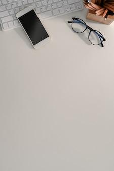 Mock-up-smartphone, drahtlose tastatur, brillen und kopienraum auf weißem schreibtisch.