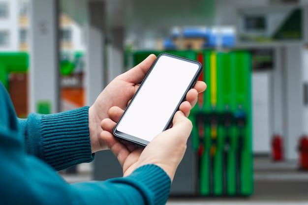 Mock-up smartphone in der hand nahaufnahme auf dem hintergrund einer tankstelle. bezahlen sie online tanken.