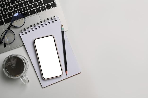 Mock-up smartphone, notizblock, kaffeetasse und laptop-computer auf weißem schreibtisch.
