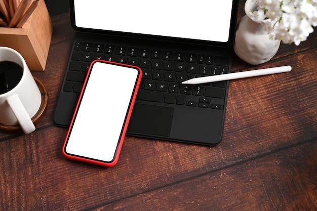 Mock-up-smartphone und computer-tablet mit weißem bildschirm auf holztisch.