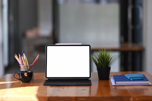 Mock-up-tablet mit drahtloser tastatur, schreibwaren und notebook auf dem schreibtisch aus holz.