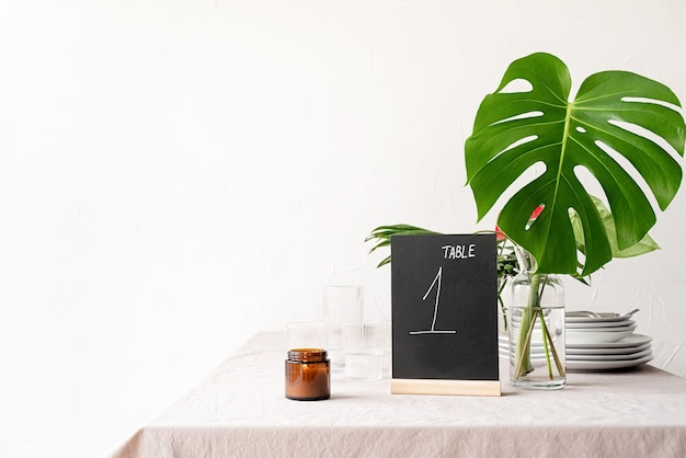 Mock up tischzelt mit worten tabelle 1 auf restauranttisch mit tropischem blumenstrauß. schwarzes kreidetischzelt