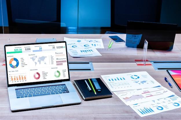 Mock-up-verkaufszusammenfassungs-diashow-präsentation auf dem display-laptop und papierkram auf dem tisch mit durchsichtiger acrylplatte trennt die mitte auf dem konferenztisch, um covid-19 im besprechungsraum zu verhindern