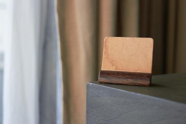 Mock up vintage braunes papierschild oder symboletikettenkartenhalter an der ecke des tisches