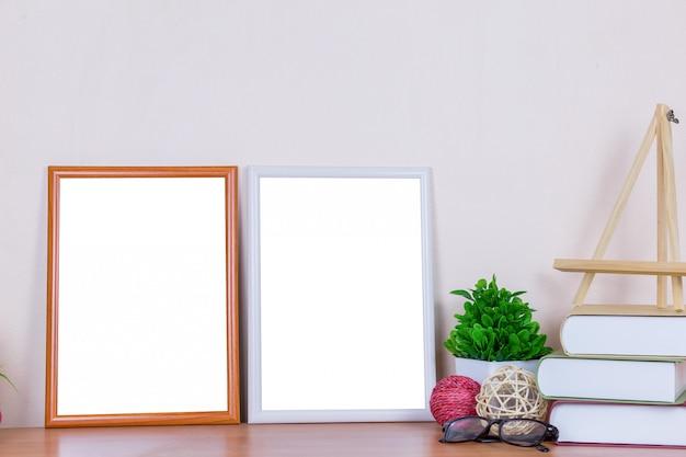 Mock up weiße und braune bilderrahmen auf holztisch