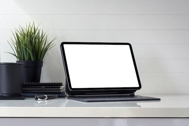 Mockup-arbeitsbereich mit leerem bildschirmtablett und zubehör auf weißem tisch.