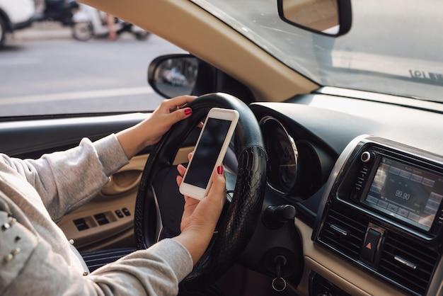 Mockup-bild der frauenhand, die mobiles smartphone mit leerem bildschirm verwendet, während sie auto fährt und das haus verlässt. beschneidungspfad.