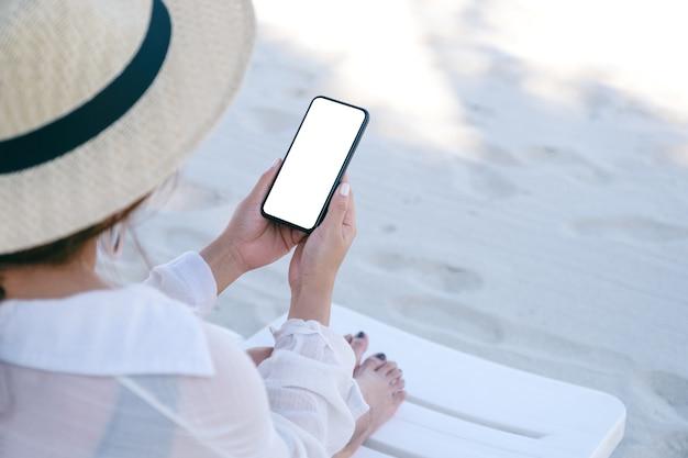 Mockup-bild einer frau, die ein schwarzes handy mit leerem desktop-bildschirm hält, während sie sich auf den strandkorb am strand legt