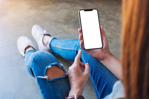 Mockup-bild einer frau, die ein schwarzes handy mit leerem weißem bildschirm hält, während sie auf dem boden sitzt