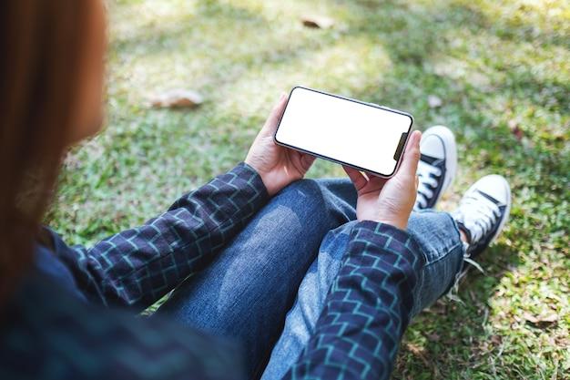 Mockup-bild einer frau, die ein schwarzes handy mit leerem weißem bildschirm hält, während sie im freien sitzt