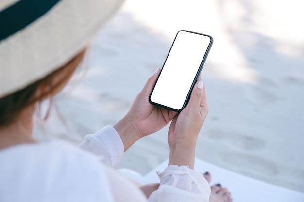 Mockup-bild einer frau, die ein weißes mobiltelefon mit leerem desktop-bildschirm hält und benutzt, während sie auf einem strandkorb am strand sitzt