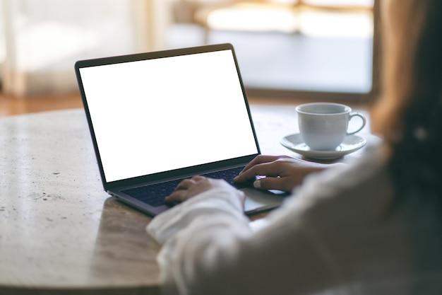 Mockup-bild einer frau, die einen laptop mit einem leeren weißen desktop-bildschirm auf dem tisch verwendet und tippt, während sie auf dem boden im haus sitzt