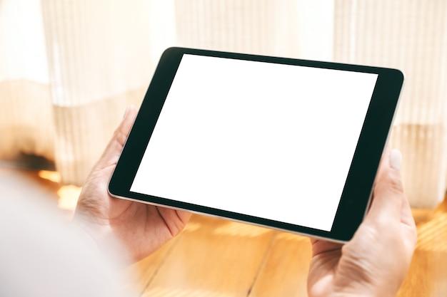 Mockup-bild einer frau, die einen schwarzen tablet-pc mit einem leeren weißen desktop-bildschirm hält, während sie sich entspannt auf den boden legt