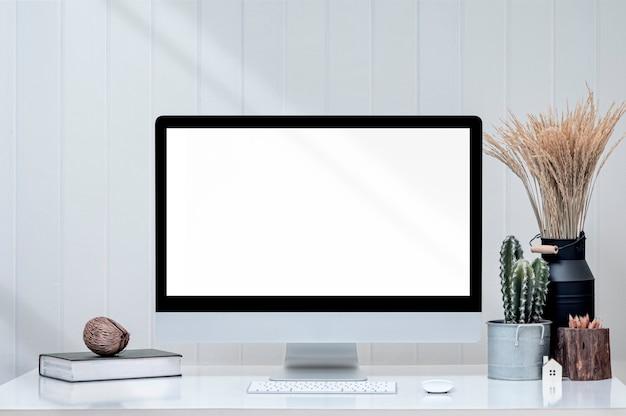Mockup blank screen monitior mit zubehör auf weißem tisch und weißer holzwand