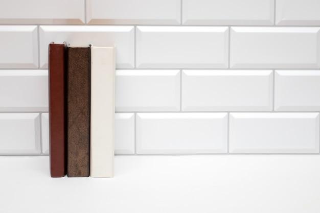 Mockup-buchregal mit leeren büchern auf weißer backsteinmauer.