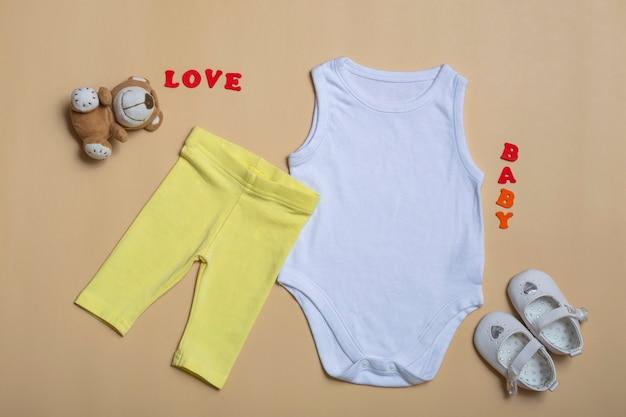 Mockup flat lay weißes babyhemd, gelbe hose, weiße schuhe mit spielzeug auf farbigem hintergrund. layout für design und platzierung von logos, werbung.