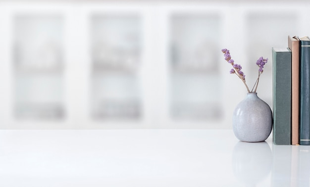 Mockup keramikvase der zimmerpflanze mit buch auf weißem tisch im modernen raum. speicherplatz kopieren.