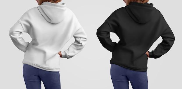 Mockup-kleidung in zwei farben. hübsche anmutige frau in einem weißen und schwarzen hoodie auf den studiohintergründen. rückenhaltung. vorlage kann in ihrem schaufenster verwendet werden.