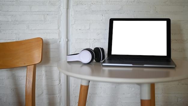 Mockup laptop leerer bildschirm und kopfhörer auf einem tisch in einem café platziert.